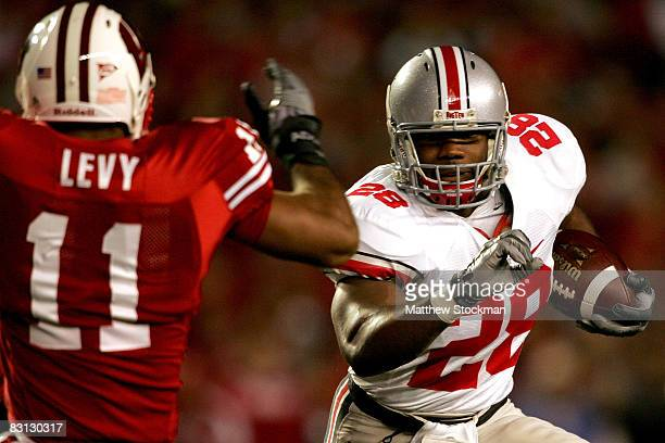 Chris Wells of the Ohio State Buckeyes attempts to elude DeAndre Levy of the Wisconsin Badgers at Camp Randall Stadium October 4 2008 in Madison...