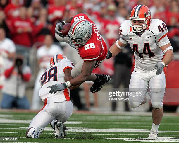 Chris Wells of the Ohio State Buckeyes is tackled by Dere Hicks of the Illinois Fighting Illini as Illinois player Brit Miller looks on during the...