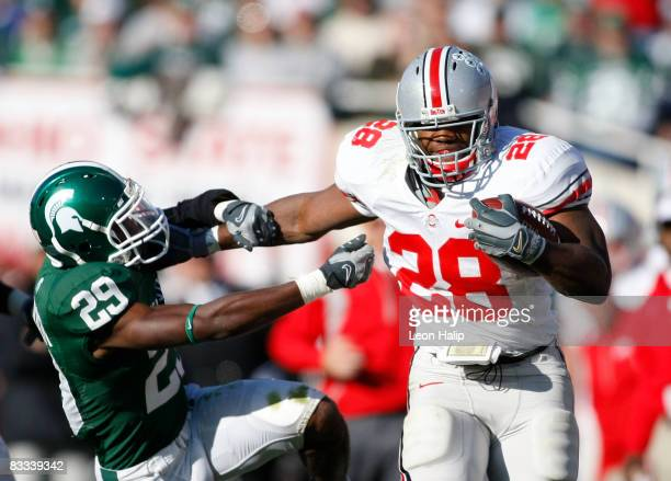 Chris Wells of the Ohio State Buckeyes stiff arms and runs for a first down against Chris Rucker of the Michigan State SPartans on October 18, 2008...