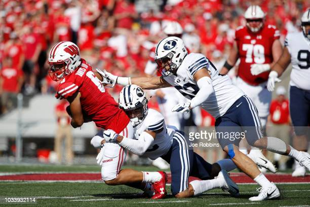 Chris Wilcox and Isaiah Kaufusi of the BYU Cougars make a tackle against Danny Davis III of the Wisconsin Badgers in the first quarter of the game at...