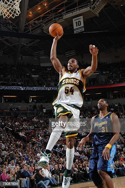 Chris Wilcox of the Seattle SuperSonics goes to the basket past the defense of Nene of the Denver Nuggets on January 23 2007 at the Key Arena in...
