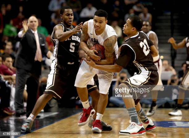 Chris Wilson of the Saint Joseph's Hawks fights for the ball with Jordan Gathers and Dion Wright of the St. Bonaventure Bonnies in the second half...
