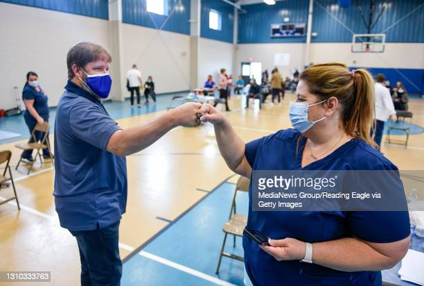 Chris Winters, the President and CEO of Olivet Boys and Girls Club, fist bumps Nurse Elizabeth Johnson. At the Olivet Boys and Girls Club Pendora...