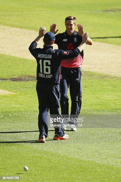 Chris Woakes and Eoin Morgan of England celebrate the dismissal of Marcus Stoinis of Australia during game one of the One Day International Series...