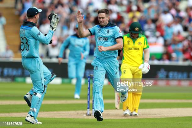 Chris Woakes of England celebrates with Jos Buttler of England after taking the wicket of David Warner of Australia during the SemiFinal match of the...