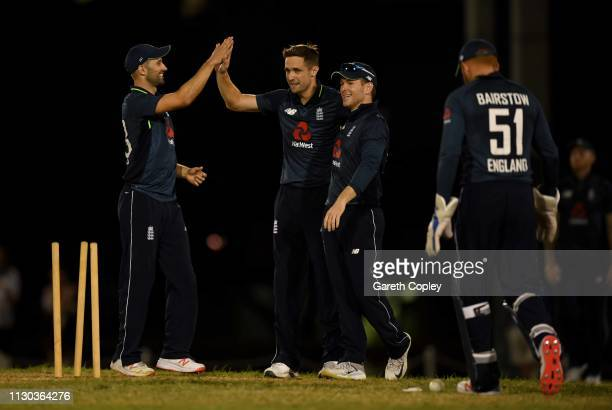 Chris Woakes of England celebrates with Mark Wood and Eoin Morgan after dismissing Akeem Jordan of The University of West Indies Vice Chancellor's...