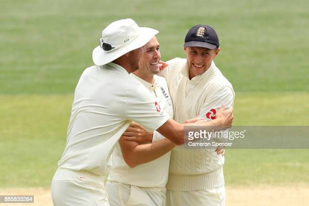 Chris Woakes of England celebrates with team mates Stuart Broad and Joe Root after taking the wicket of Tim Paine of Australia during day four of the...