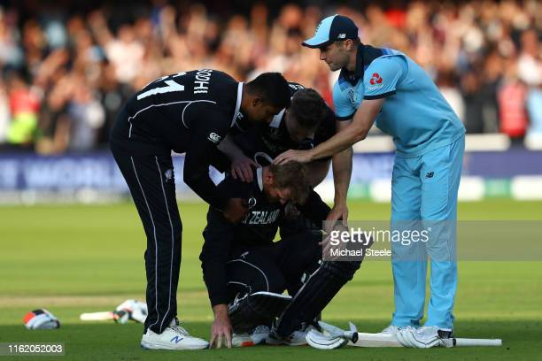 Chris Woakes of England offers his support 11to Martin Guptill of New Zealand following the SuperOver as Jimmy Neesham and 1 console their team mate1...