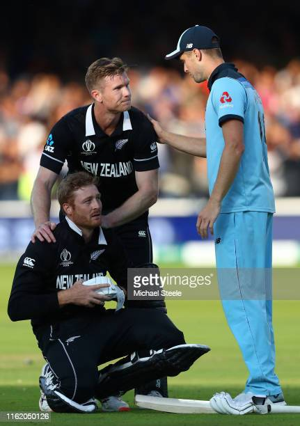 Chris Woakes of England offers his support to Martin Guptill and Jimmy Neesham of New Zealand following the Super-Over during the Final of the ICC...