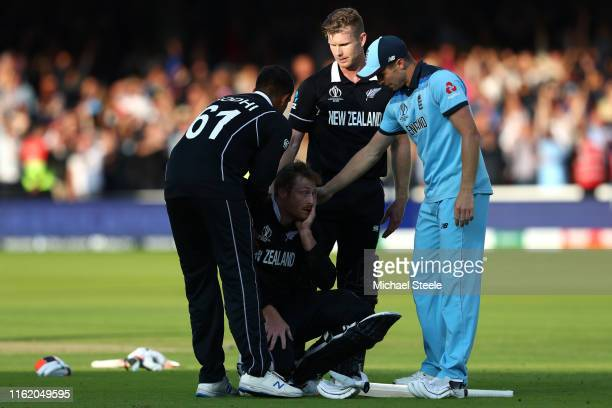 Chris Woakes of England offers his support to Martin Guptill of New Zealand following the Super-Over as Jimmy Neesham and 1 console their team mate1...
