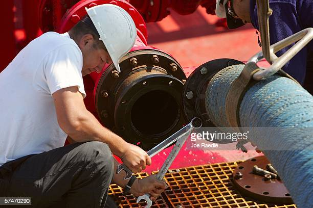 Chris Wolf and Robert Ezekiel work on a hose used to off-load fuel from a barge at the Global Petroleum facility April 27, 2006 in Boston,...