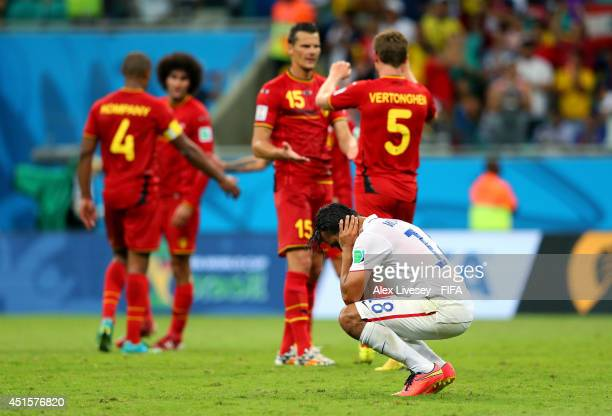 Chris Wondolowski of the United States reacts after the defeat while Belgium players celebrate after the 2014 FIFA World Cup Brazil Round of 16 match...