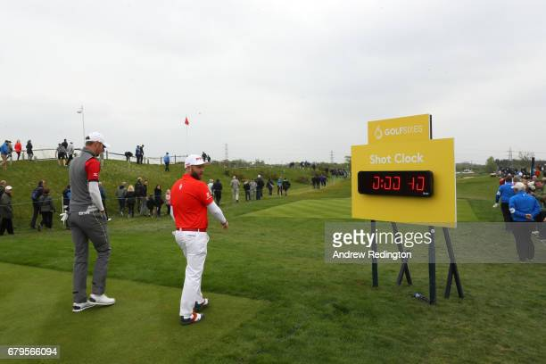Chris Wood and Andy Sullivan of England walk past the shot clock on the 4th hole during the Group A match between England and India during day one of...