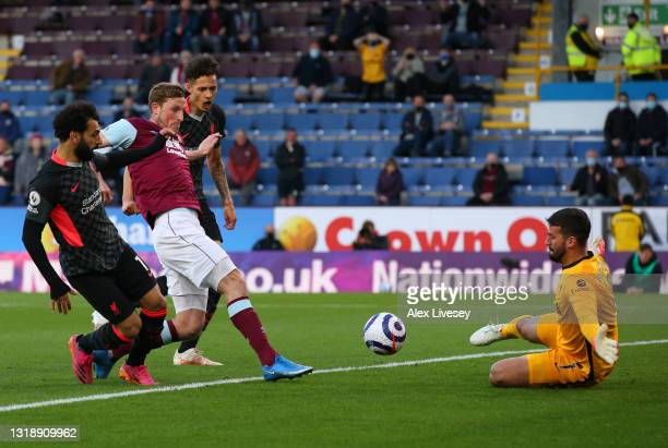 Chris Wood of Burnley has a shot saved by Alisson of Liverpool whilst under pressure from Mohamed Salah of Liverpool during the Premier League match...