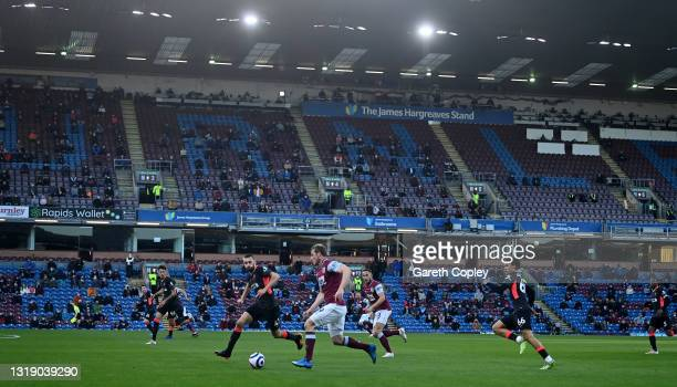 Chris Wood of Burnley runs with the ball as fans social distance in the stand during the Premier League match between Burnley and Liverpool at Turf...