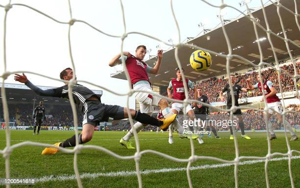 Chris Wood of Burnley scores his team's first goal past a challenge from Christian Fuchs of Leicester City during the Premier League match between...