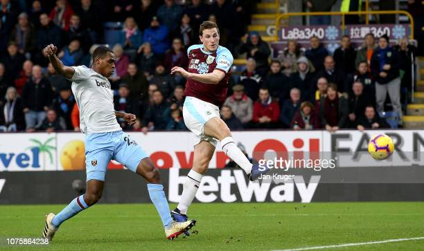 Chris Wood of Burnley scores his team's first goal while under pressure from Issa Diop of West Ham United during the Premier League match between...