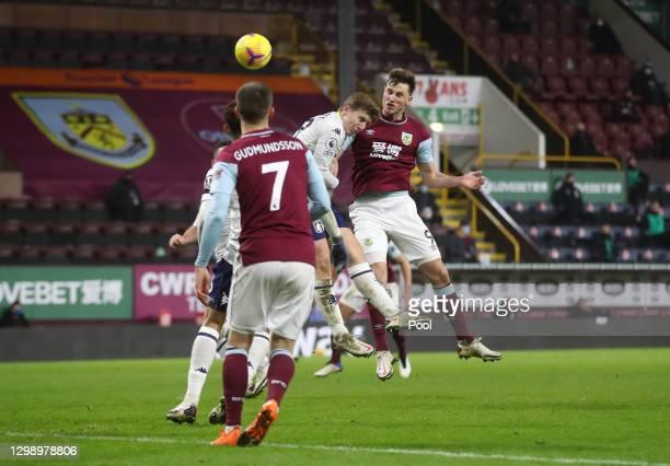 Chris Wood of Burnley scores their side's third goal whilst under pressure from Matt Targett of Aston Villa during the Premier League match between...