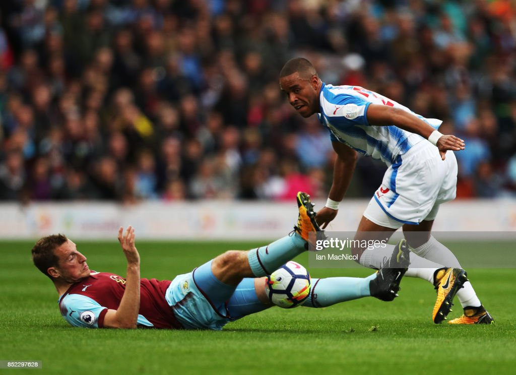 Chris Wood of Burnley vies with Mathias Zanka Jorgensen of Huddersfield Town during the Premier League match between Burnley and Huddersfield Town at Turf Moor on September 23, 2017 in Burnley, England.