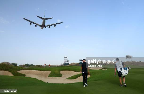 Chris Wood of England and his caddie walk along the 14th hole as a airplane passes overhead during day two of the Oman Open at Al Mouj Golf Complex...