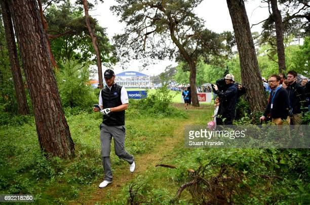 Chris Wood of England attempts to find his ball in the trees on the 18th hole during day four of the Nordea Masters at Barseback Golf Country Club on...