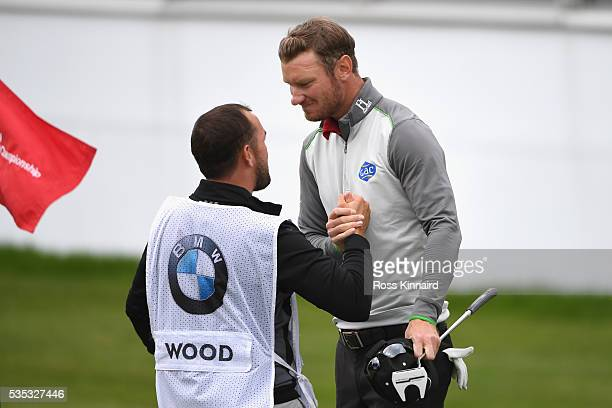 Chris Wood of England celebrates victory on the 18th green with caddie Mark Crane during day four of the BMW PGA Championship at Wentworth on May 29...