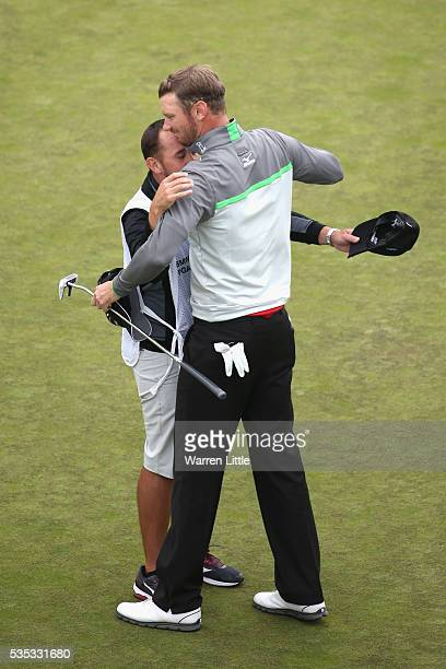 Chris Wood of England celebrates victory on the 18th green with caddie Mark Crane during day four of the BMW PGA Championship at Wentworth on May 29,...