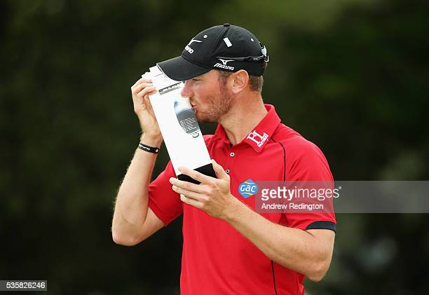 Chris Wood of England kisses the trophy following his victory during day four of the BMW PGA Championship at Wentworth on May 29, 2016 in Virginia...
