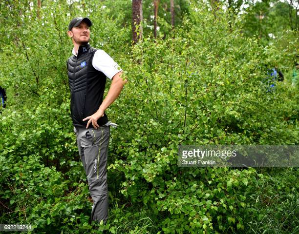 Chris Wood of England looks on after playing into the trees on the 18th hole during day four of the Nordea Masters at Barseback Golf Country Club on...
