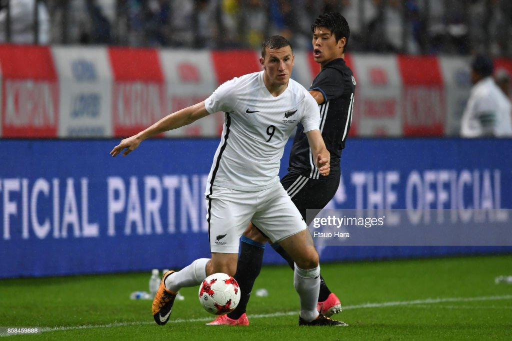 Chris Wood of New Zealand controls the ball under pressure of Hiroki Sakai of Japan during the international friendly match between Japan and New Zealand at Toyota Stadium on October 6, 2017 in Toyota, Aichi, Japan.