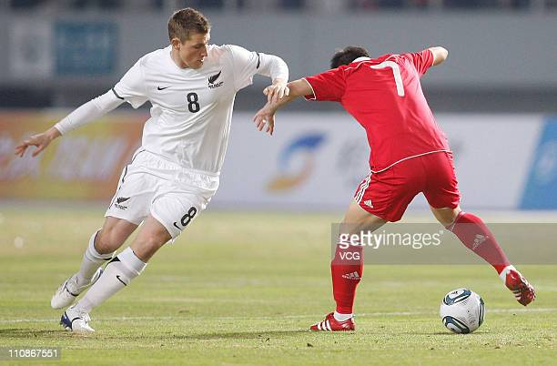 Chris Wood of New Zealand fights for a ball with Cui Peng of China during the international friendly match between China and New Zealand at Wuhan...