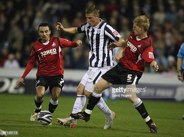 Chris Wood of West Bromwich Albion is tackled by Leon Britton and Alan Tate during the Coca Cola Championship match between West Bromwich Albion and...