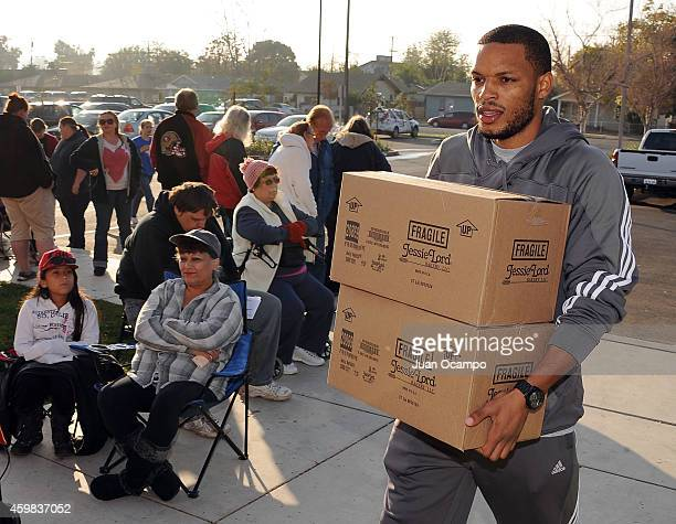 Chris Wright of the Bakersfield Jam helps carry food items into the gym during the Bakersfield Jam Thanksgiving Box Give Away Event on November 26...
