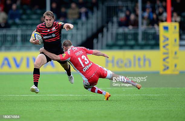 Chris Wyles of Saracens beats the tackle of Henry Trinder of Gloucester during the Aviva Premiership match between Saracens and Gloucester at Allianz...