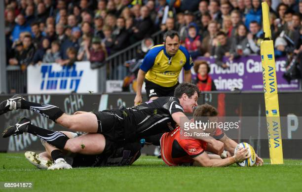 Chris Wyles of Saracens dives past the tackles from Jack Nowell and Ian Whitten of Exeter Chiefs to score his team's first try during the Aviva...