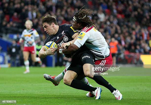 Chris Wyles of Saracens goes over despite the tackle from Marland Yarde of Harlequins to score his team's fourth try during the Aviva Premiership...
