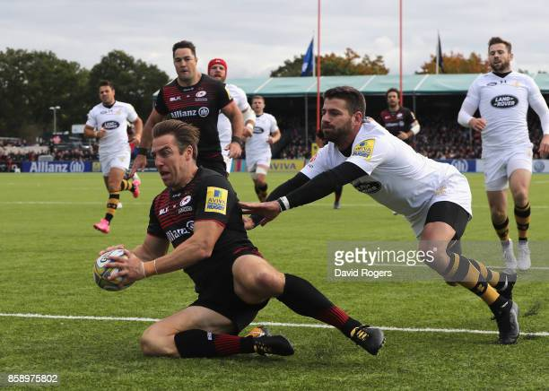 Chris Wyles of Saracens scores the first try as Willie le Roux attempts to tackle during the Aviva Premiership match between Saracens and Wasps at...