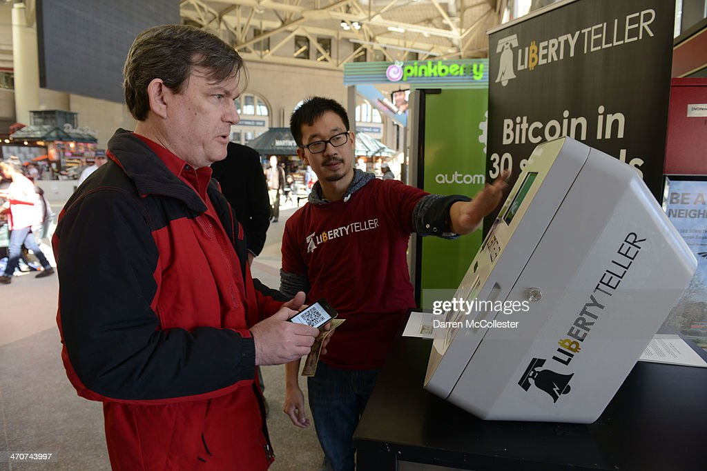 Chris Yim of Liberty Teller helps Paul Watts (L) with a newly installed Bitcoin ATM at South Station February 20, 2014 in Boston, Massachusetts. The ATM was placed by Liberty Teller to help inform people about the digital currency, which can be bought and sold anonymously, and can be used at a number of online retailers in place of cash or credit cards.