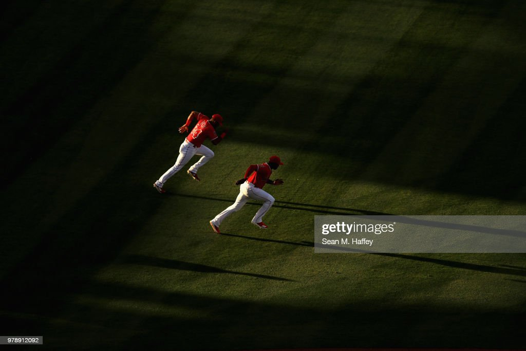 Chris Young #24 and Justin Upton #8 of the Los Angeles Angels of Anaheim warm up prior to a game against the Arizona Diamondbacks at Angel Stadium on June 19, 2018 in Anaheim, California.