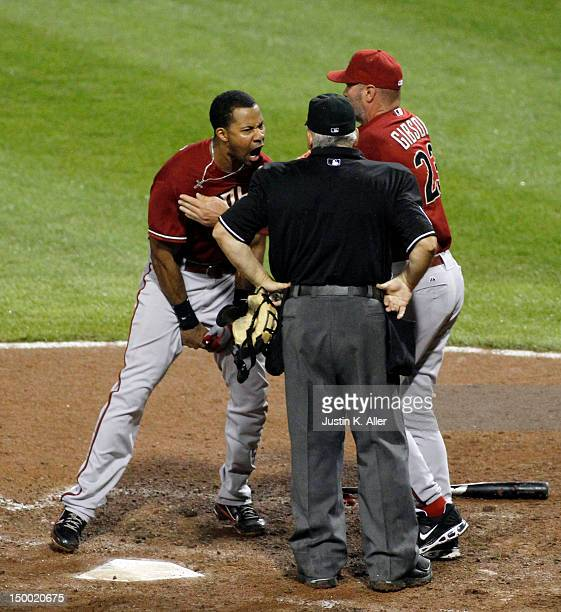 Chris Young of the Arizona Diamondbacks screams at home plate umpire Larry Vanover while being restrained by manager Kirk Gibson after striking out...
