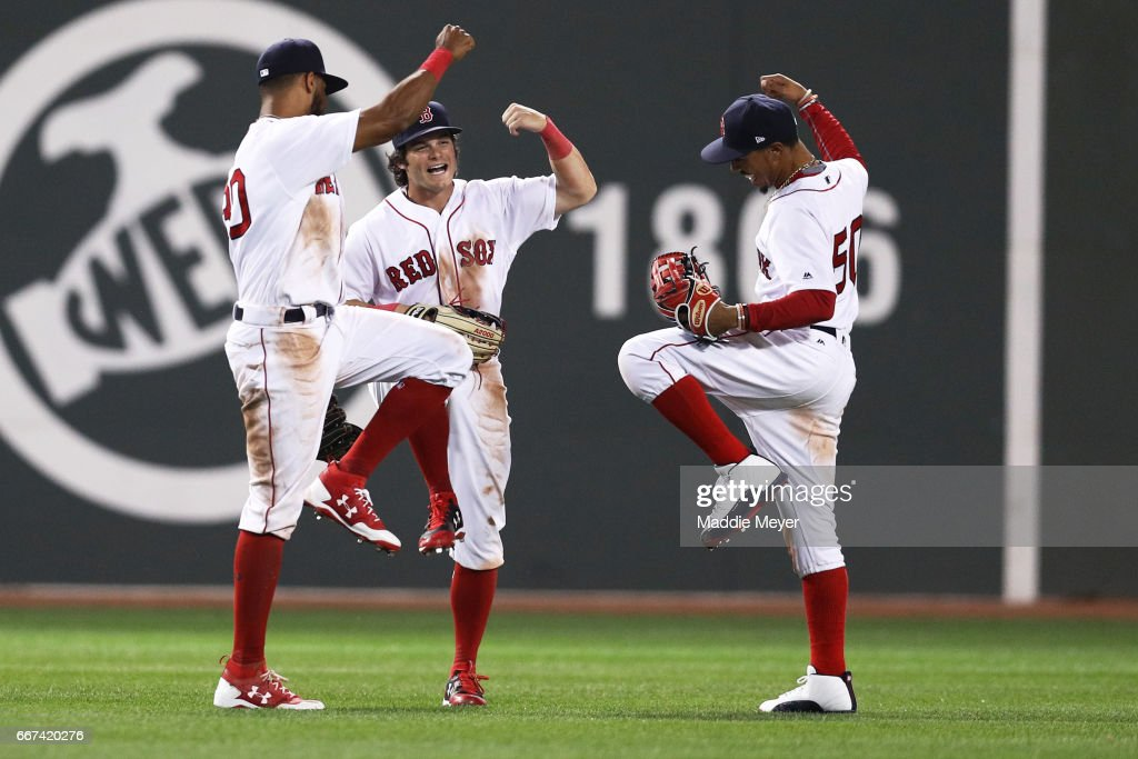 Chris Young #30 of the Boston Red Sox, Andrew Benintendi #16, and Mookie Betts #50 celebrate their 8-1 win over the Baltimore Orioles at Fenway Park on April 11, 2017 in Boston, Massachusetts.