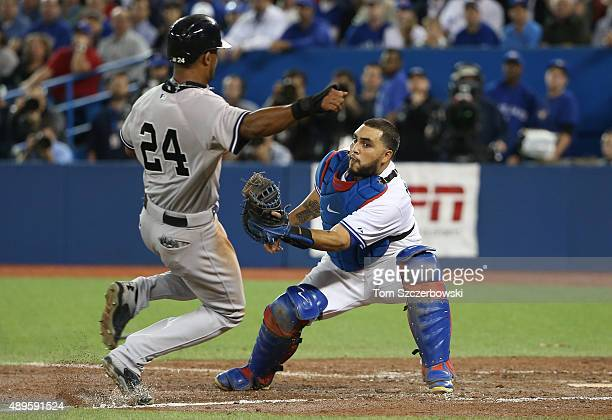 Chris Young of the New York Yankees is tagged out at home plate as he tries to score on a sacrifice fly attempt in the ninth inning during MLB game...