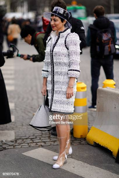 Chrisa Pappas wears a transparent hat a tweed white coat white shoes outside Chanel during Paris Fashion Week Womenswear Fall/Winter 2018/2019 on...