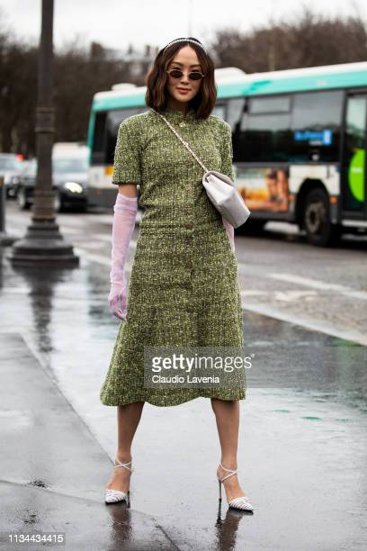 Chriselle Lim wearing a long green dress sheer gloves white heels and white Chanel bag is seen outside Chanel on Day 9 Paris Fashion Week...