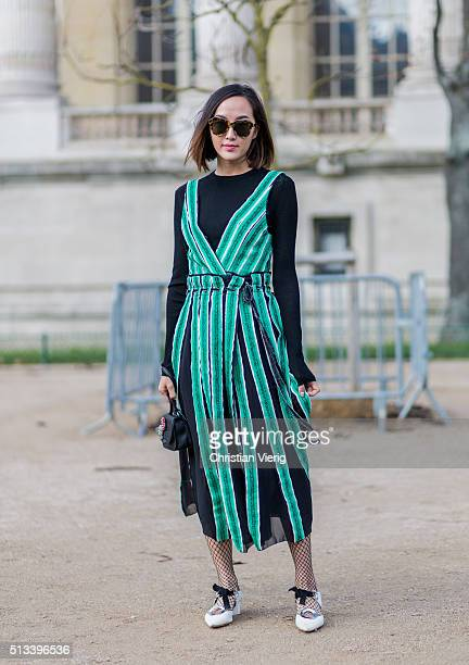 Chriselle Lim wearing A Proenza Schouler green black striped dress and white heels outside Maison Margiela during the Paris Fashion Week Womenswear...