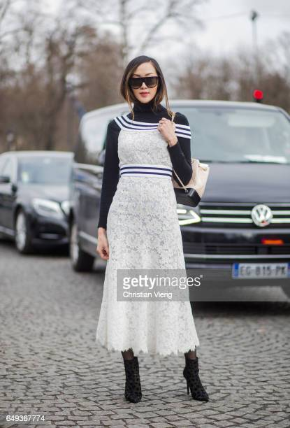 Chriselle Lim wearing a white laced dress Chanel backpack outside Chanel on March 7 2017 in Paris France