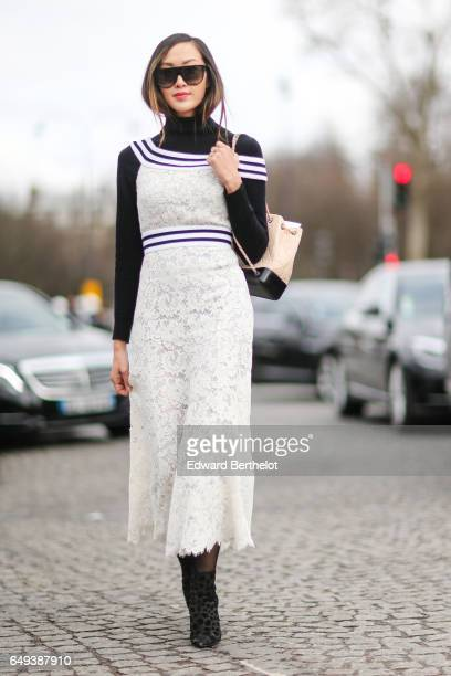 Chriselle Lim wears a Chanel lace white dress outside the Chanel show during Paris Fashion Week Womenswear Fall/Winter 2017/2018 on March 7 2017 in...
