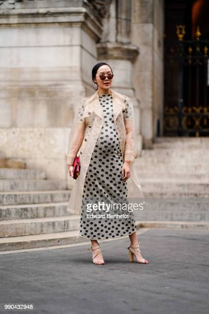 Chriselle Lim wears a trench coat and a dress with polka dots outside Schiaparelli during Paris Fashion Week Haute Couture Fall Winter 2018/2019 on...