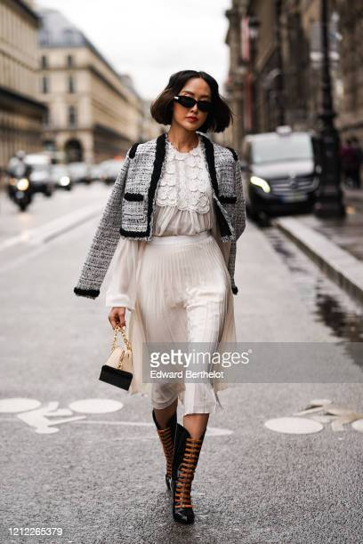 Chriselle Lim wears sunglasses, a heather black tweed crop jacket with a black trim, a white lace gathered long sleeved top, a white flowing pleated...