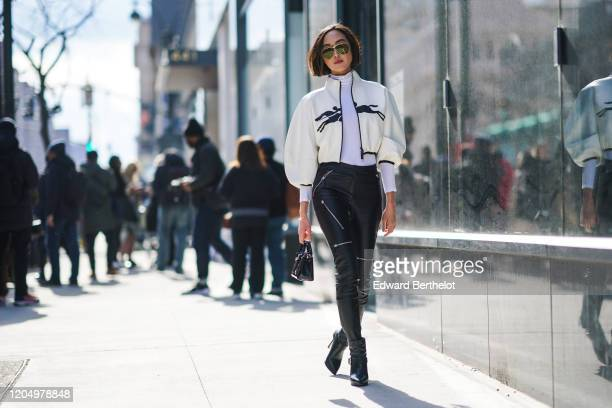 Chriselle Lim wears sunglasses, a Longchamp white jacket with puff sleeves, a white top, black leather pants, a bag, outside Longchamp, during New...